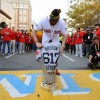 Jonny Gomes brings the 2013 World Series Championship Trophy to the finish line of the Boston Marathon.