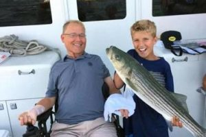 Travis Roy and Jack Butterworth with a striper they caught off Martha's Vineyard. (PHOTO COURTESY OF JOHN BUTTERWORTH AND BOSTON GLOBE)